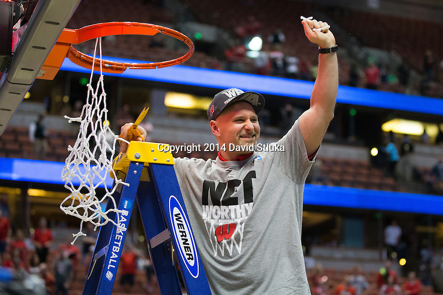 Wisconsin Badgers Strength and Conditioning Coach Erik Helland cuts down a piece of the net after the Western Regional Final NCAA college basketball tournament game against the Arizona Wildcats Saturday, March 29, 2014 in Anaheim, California. The Badgers won 64-63 (OT). (Photo by David Stluka)