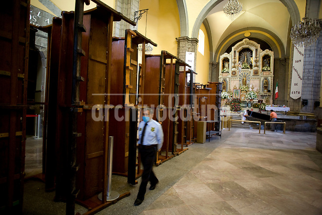 A guard walks through an empty church since catholic authorities decided to close all the churches in Mexico DF to prevent swine flu ,an epidemic spreading  fast through the country