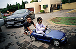 Lebone Dube (r), age 4, and a friend, play with a model BMW car in the driveway on February 15, 2004 in Cedar Lake, an up-market community in Johannesburg, South Africa. Her father, Oscar Dube, works for the mobile phone equipment maker Ericsson. They belong to a new black elite. Lebone attends an exclusive pre-school with mostly white children. Well educated and connected, they have risen from the townships to a new lifestyle, since the fall of Apartheid and the start of democracy in 1994. (Photo by: Per-Anders Pettersson)...