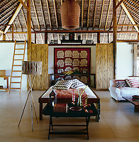 An antique Suzani, Balinese daybed and bespoke bamboo standard lamp furnish the main living area