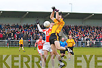 Bryan McGuire of Listowel Emmets jumping for the ball on the hop while being challenged by Brosna's Timmy Finnegan.