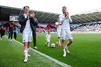 George Byers (left) and Matt Grimes of Swansea City applauds the fans at the final whistle during the Sky Bet Championship match between Swansea City and Hull City at the Liberty Stadium in Swansea, Wales, UK. Saturday 27 April 2019