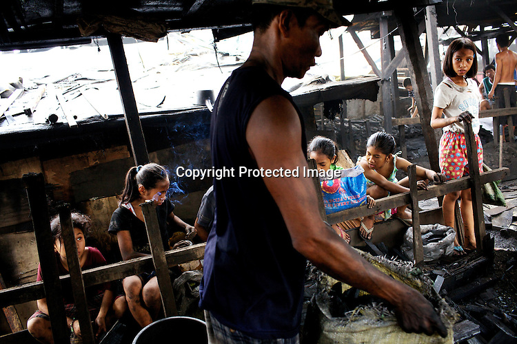 Children wait along the fence to scavenge the charcoal while a family works together to pack charcoal into the bags around the wood-ovens in the slums of Smokey Mountain-II in Manila in Philippines. Photo: Sanjit Das