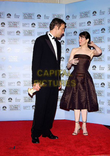 CLIVE OWEN & RENEE ZELLWEGER.62nd Annual Golden Globe Awards at The Beverly Hilton Hotel Hotel, Los Angeles, California. Pressroom.January 16th, 2005 .full length, brown silk satin ripple pattern strapless dress, award trophy, tuxedo, touching hair.www.capitalpictures.com.sales@capitalpictures.com.©Capital Pictures