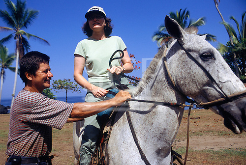Marenco, Osa Peninsula, Costa Rica. Tourist on horseback with a guide on the beach.
