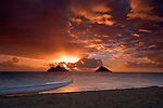 Surise over Mokulua Islands from Lanikai Beach with outrigger canoe in foreground.