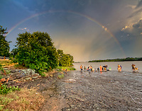 Photographers photographing a rainbow on the Arkansas River after a rain storm at Wilson Rock, near Muldrow Oklahoma.