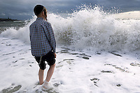 An Hasidic boy paddles in the sea as waves approach on a beach in Aberystwyth..