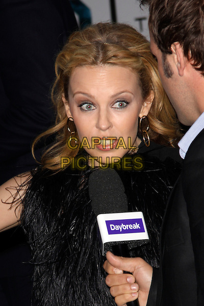 KYLIE MINOGUE.'The Kid' UK premiere held at the Odeon West End, Leicester Square, London, England..September 15th, 2010.headshot portrait marabou fluffy fur furry collar sleeveless gold hoop earrings daybreak microphone interview funny .CAP/AH.©Adam Houghton/Capital Pictures...