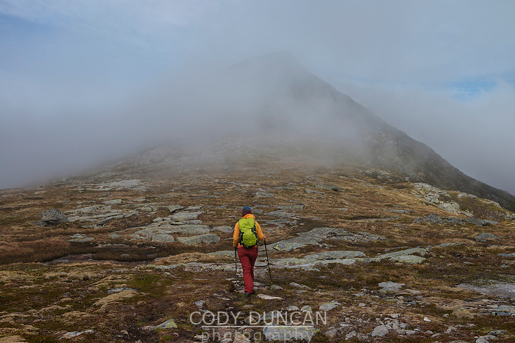 Female hiker hiking through cloudy weather towards summit of Volandstind mountain peak, Flakstadøy, Lofoten Islands, Norway