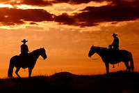 Pair of Cowboys on horse back on a rise at Sunset