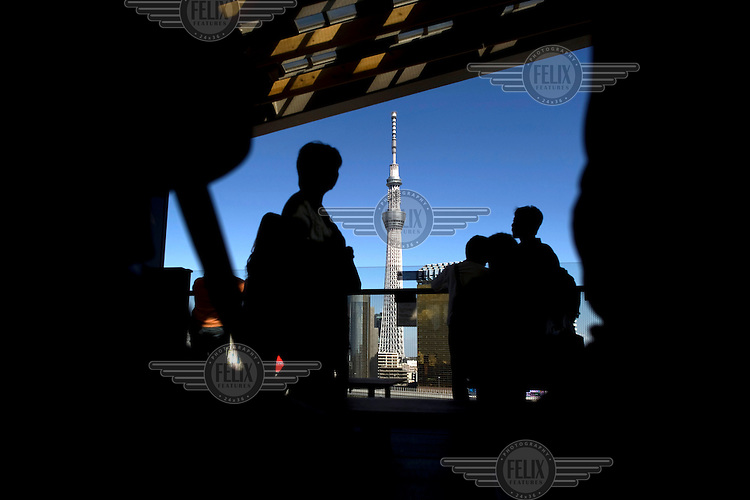 People looking towards the Tokyo Sky Tree Tower in Ryogoku. At 634 meters the tower is one of the tallest buildings in the world. /Felix Features