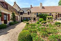 France, Cher (18), Apremont-sur-Allier, labellisé Plus Beaux Villages de France, cour fleurie dans le village avec buies taillées , ails défleuries, renouées, puits et lierre