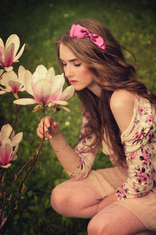 Young girl with pale skin and long blond hair dressed in a pale pink dress and floral cardigan sitting outdoors in a garden and smelling magnolia flowers