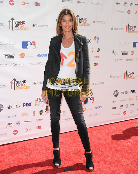 CINDY CRAWFORD .at Stand Up to Cancer held at Sony Picture Studios in Culver City, California, USA, September 10th 2010.     .full length white t-shirt jacket jeans ankle boots cork platform biker leather chains belt                                                                    .CAP/RKE/DVS.©DVS/RockinExposures/Capital Pictures.