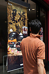A man looks at an advertisement of the Burger King's new black burgers on display outside the Shinjuku store on August 21, 2015, Tokyo, Japan. The chain's two new black burgers use bamboo charcoal-infused buns and cheese, Black Hashed Sauce (a mix of red wine, squid ink, onions, tomato and crushed garlic), and slices of grilled eggplant. In July Burger King launched two red burgers in another Japan only colored burgers promotion. The two new black burgers are the Kuro Shogun costing 690 JPY (5.59 USD) and the Kuro Taisho costing 590 JPY (4.78 USD). They will be on sale for a limited time in Burger King's Japanese stores from August 21st. (Photo by Rodrigo Reyes Marin/AFLO)