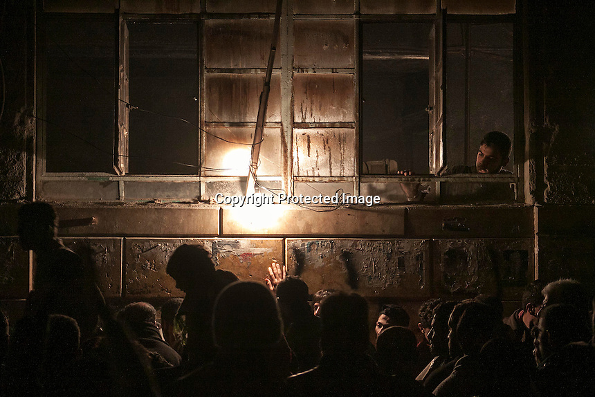 In this Sunday, Dec. 09, 2012 photo, night falls as crowds of Syrians queue for bread at a bakery in an area controlled by rebel fighters in the Tarik Al-Bab neighborhood of Aleppo, Syria. (AP Photo/Narciso Contreras)