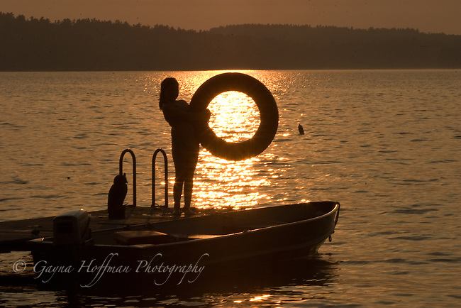 Girl holding innertube, silhouetted in sunset. Lake, NH