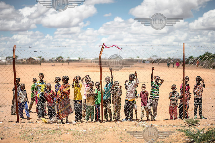 Children stare through the boundry fence at Dadaab Refugee Camp, home to some 350,000 people mostly from Somalia. A third generation of people are now being born in the camp. Every time a mayor terror attack takes place in Kenya voices in Kenyan society and politics call for closure of the refugee camp claiming that it is a breeding ground for terrorists, and Al-Shabaab in particular. The camp is located in a remote area, around 80 kilometres from the Somali border, visitors are required to travel with armed escort and the entrances to UN facilities are fortified and guarded. The UNHCR has registered all refugees on a computer database.