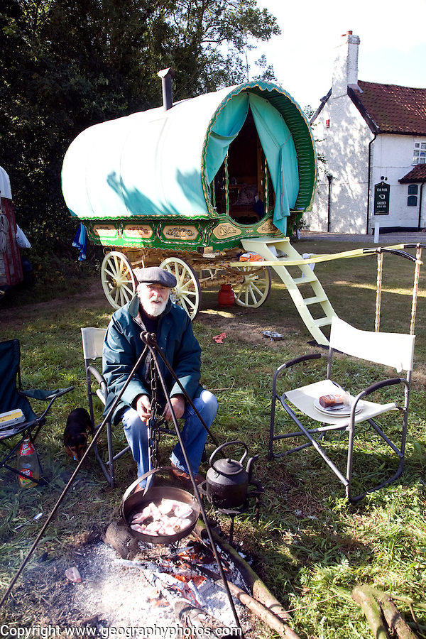 Man cooking his breakfast on open fire by his gypsy caravan, Saxtead Green, Suffolk, England