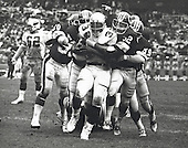 St. Louis Cardinals running back Ottis Anderson (32) is gang tackled by a hoard of Washington Redskins defenders including right outside linebacker Pete Wysocki (50), right defensive end Coy Bacon (79), who is behind Anderson, middle linebacker Neal Olkewicz (52), and left outside linebacker Brad Dusek (59) on the Redskins 35 yard line during the game at RFK Stadium in Washington, DC on November 11, 1979.  Cardinals left tackle Keith Wortman (62) is at left.  The Redskins won the game 30 -28.<br /> Credit: Arnie Sachs / CNP
