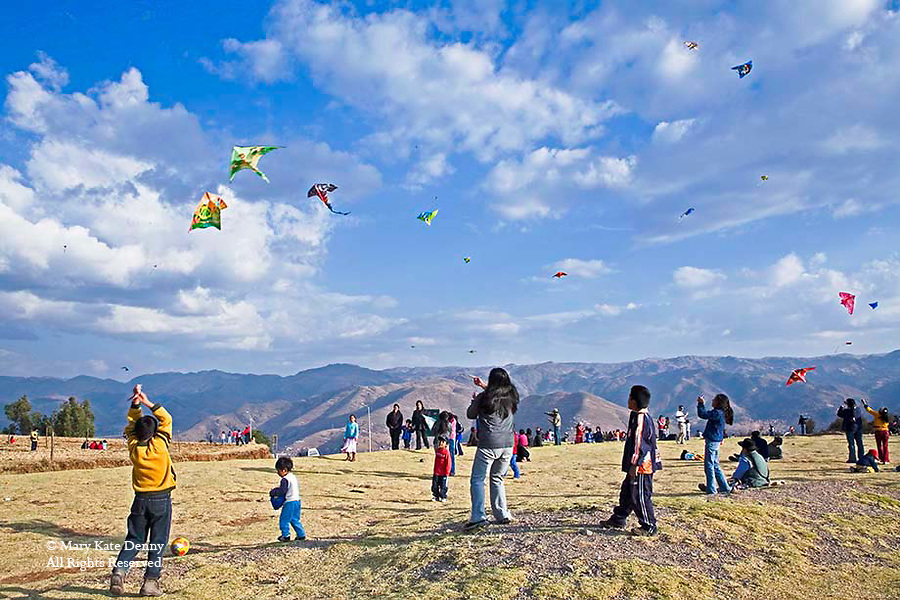 Boys,girls and adults fly kites in clear blue skies at Sacsayhuaman Park near Cuzco,Peru
