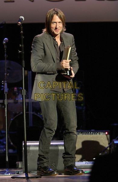 KEITH URBAN (receiving the Jim Reeves International Award).The Academy of Country Music held their annual Honors Awards show at the Ryman auditorium, Nashville, TN, USA..September 20th, 2010.ACM full length stage black suit jacket microphone grey gray trophy award jeans denim.CAP/ADM/DH.©Dan Harr/AdMedia/Capital Pictures.