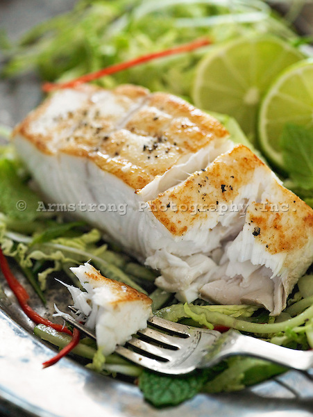 Seared halibut fillet on green salad with fork
