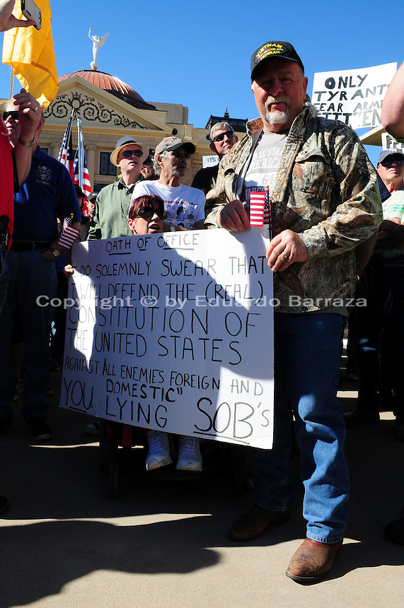 "Phoenix, Arizona. January 19, 2013 - A protester who attended Saturday's rally in Phoenix opposes the president's proposed changes to gun laws in America by holding a sign that parodies a government official's oath of office. As President Barack Obama proposed new gun regulations last week, gun owners demonstrated against it with national ""Guns Across America"" rallies to defend the Second Amendment. Dozens showed up at the Arizona State Capitol, many of them carrying weapons. Photo by Eduardo Barraza © 2013"