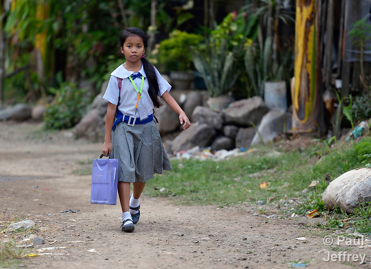 A girl walks to school in the Suburban neighborhood of Rodriguez, Rizal, in the Philippines. Most of the community's families were relocated here from other area of Manila and the nearby countryside to make way for urban renewal projects or to move them out of harm's way. Yet the new community was hit hard by Typhoon Ketsana in 2009, and Christian Aid, a member of the ACT Alliance, provided emergency relief supplies. Over the years since, with help from Christian Aid and other groups, community members have organized themselves and engaged in a process of disaster risk reduction, including identifying and mapping high-risk zones and evacuation routes in their area. Christian Aid has also assisted with financial and technical support for income generating livelihood projects and community enterprises.