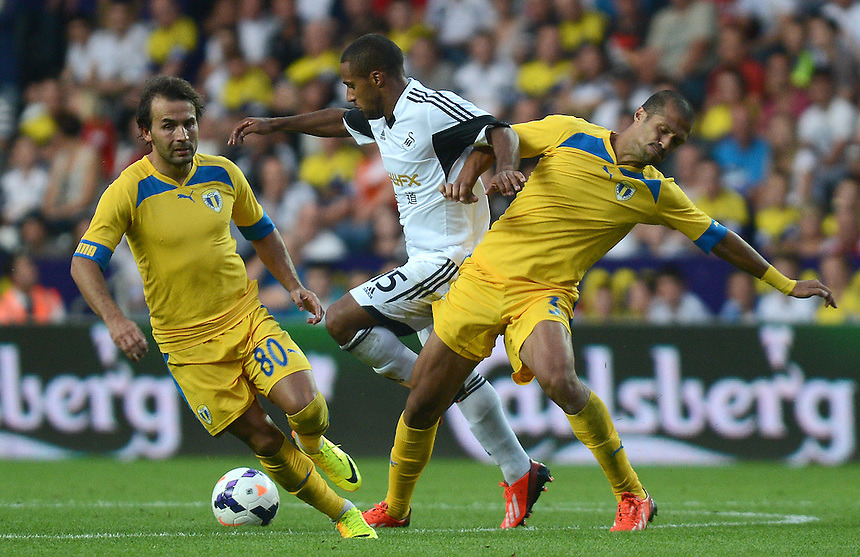 Swansea City's Wayne Routledge battles with Petrolul Ploiesti's Felipe Teixeira and Geraldo<br /> <br /> (Photo by Ian Cook/CameraSport)<br /> <br /> Football - UEFA Europa League Qualifying Play-off First leg - Swansea City v Petrolul Ploiesti - Thursday 22nd August 2013 - The Liberty Stadium - Swansea<br /> <br /> &copy; CameraSport - 43 Linden Ave. Countesthorpe. Leicester. England. LE8 5PG - Tel: +44 (0) 116 277 4147 - admin@camerasport.com - www.camerasport.com