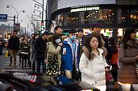 Una giovane coppia in una strada nella zona commerciale della citt&agrave;.<br /> People walking on the commercial street