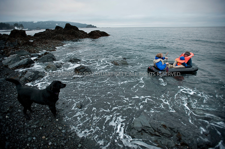 12/11/2009--Seldovia, Alaska, USA..Erin McKittrick, with her son, Katmai, and her husband Bretwood Higman test a new raft on a beach in Seldovia, Alaska while their dog Panda looks on. In 2010, the family will use the raft during a trip to the Alaskan arctic, China, and the Lost Coast in Alaska to look at how carbon currently fossilized in Alaska coal might be burned and change Alaska's (and the world's) climate...McKittrick grew up in Seattle and met Higman, from Seldovia, at Carleton College in 2001. In June 2007, the couple left Seattle for the Aleutian Islands, traveling 4000 miles solely by human power through some of the most rugged terrain in the world; their adventure has recently been published in a book written by McKittrick with Hig's photographs titled, 'A Long Trek Home: 4,000 Miles by Boot, Raft, and Ski'...Together, the couple also run a small environmental non-profit, Ground Truth Trekking, which uses trekking to explore the complexities of natural resource issues. The couple lives with their 10 month old son son, Katmai, in Seldovia, Alaska, a 300 person village just off the end of the road system...©2009 Stuart Isett. All rights reserved.
