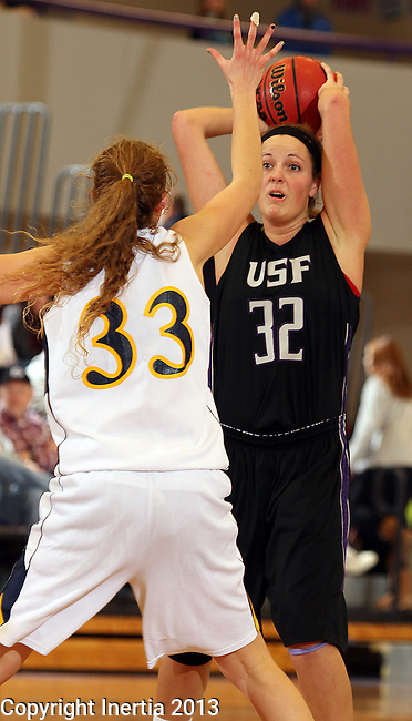 SIOUX FALLS, SD - DECEMBER 7:  Laura Johnson #32 from the University of Sioux Falls looks for a teammate while being guarded by Hayley McCarron #33 from Augustana in the second half of their game Saturday evening at the Stewart Center. (Photo by Dave Eggen/Inertia)