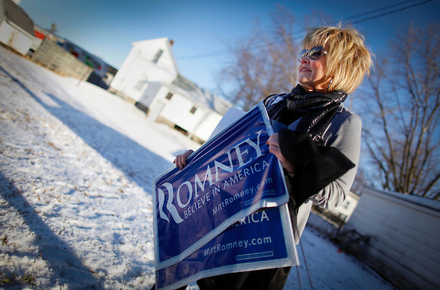 After collecting a few campaign signs, Carey Pomykata of Omaha, Neb. waits to catch a glimpse of Mitt Romney while standing near his tour bus in Atlantic, Iowa on Sunday, January 1, 2012.  (Christopher Gannon/GannonVisuals.com/MCT)