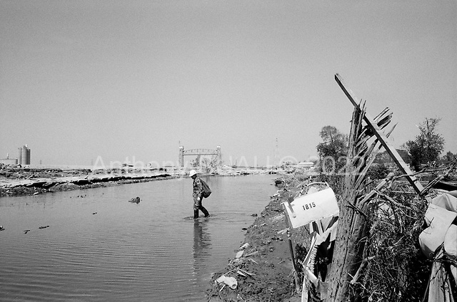New Orleans, Louisiana.USA.September 28, 2005 ..At the exact point where the levy broke in New Orleans' lower 9th district Michael LaGarde, 33 years old, finds what remains of his home ... a mound of dirt and a few small items pushed aside by a massive barge that came through the levy when it broke...He was born and raised in this house and lived with his 3 children in the house before the hurricane and flood took it away. His grandparents built the house in 1940. It was 65 years old...The broken levy is just behind him and the barge where is home once was as he strolls through the streets he once knew intimately.