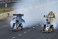 Jul. 19, 2014; Morrison, CO, USA; NHRA top fuel driver Tony Schumacher (right) slows down alongside Bob Vandergriff Jr during qualifying for the Mile High Nationals at Bandimere Speedway. Mandatory Credit: Mark J. Rebilas-