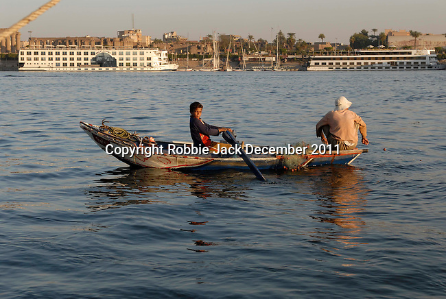 Fishing from a small boat on the River Nile at Luxor.The town of Luxor occupies the eastern part of a great city of antiquity which the ancient Egytians called Waset and the Greeks named Thebes.