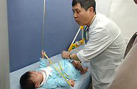 An adopted Chinese baby girl is measured during a final health inspection in Guangzhou, before they leave China for a new lives in America. Over 10,000 babies, all girls or disabled boys, are adopted from China annually.