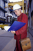 Pocerady Power Station, Czech Republic.  Man wearing a white safety hat looking at notes in a blue folder.