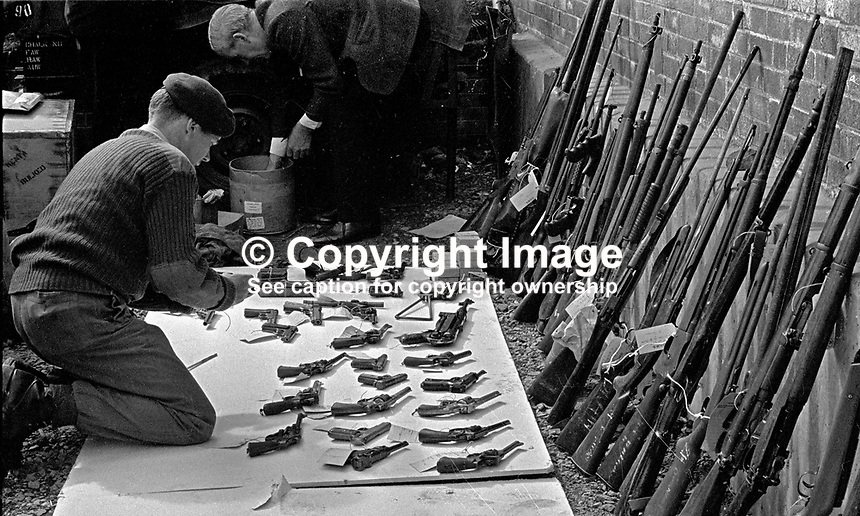 Soldier puts on display handguns, rifles, ammunition, etc, found during an intensive search of the area. 197007030251m. The British Army imposed during July 3 & 4, 1970, a 34 hour curfew (except for a two hour break to allow shopping) in approximately 50 streets in the Lower Falls district of Belfast, N Ireland, UK. A military helicopter hover overhead warning people they would be arrested if they remained on the streets. An army search during the curfew uncovered 100 firearms, 100 home-made bombs, 250 lbs of explosives, 21000 rounds of ammunition and 8 two-way radios. This curfew is often seen as a turning point in souring relations between the Roman Catholic working class and the British Army. The army was no longer seen as the protector of the Catholic community...Copyright Image from Victor Patterson, 54 Dorchester Park, Belfast, UK, BT9 6RJ..Tel: +44 28 9066 1296.Mob: +44 7802 353836.Voicemail +44 20 8816 7153.Skype: victorpattersonbelfast.Email: victorpatterson@mac.com.Email: victorpatterson@ireland.com (back-up)..IMPORTANT: If you wish to use this image or any other of my images please go to www.victorpatterson.com and click on the Terms & Conditions. Then contact me by email or phone with the reference number(s) of the image(s) concerned.