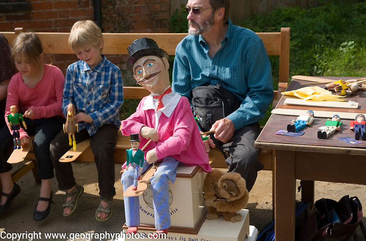 Man and children operating a traditional wooden jig doll dancer during a country folk event at Shottisham, Suffolk, England