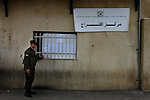 "A Palestinian security guard at the entrance to the Mukata'ah, the Palestinian governmental headquarters at the West Bank city of Ramallah, during election day for the Palestinian parliament. The sign reads: ""Polling Station""."
