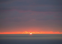 The setting sun provides a bright orange backlight to nearby clouds, as seen from Kailua-Kona, Big Island.