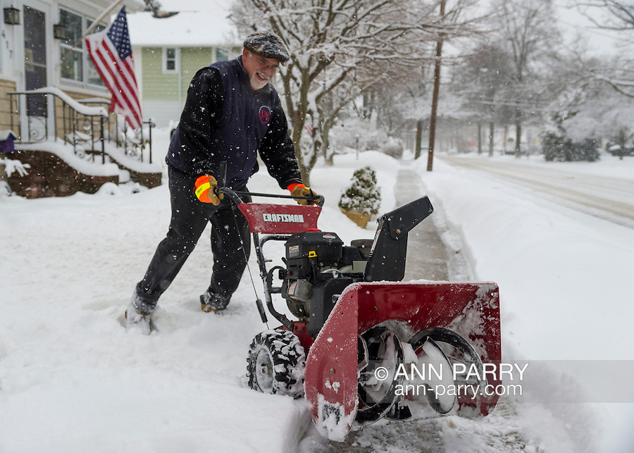 March 5, 2015. Merrick, New York, United States. Artie uses his snow blower to help out and clear the sidewalk in front of his neighbor's house as snow is falling yet again on the south shore of Long Island, which is receiving the heaviest snow on L.I., with an accumulation of 6 to 8 inches expected. Many schools closed due to hazardous travel conditions, and a Winter Weather Watch is in effect until 7 PM.