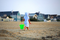 A well protected and ready for sand castle building child walks to get more sand @ VA Beach, VA