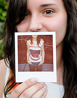 Nicki Meyer of Spokane holds a Polaroid photo depicting the graphic t-shirt and jeans she wore to the 2011 Bumbershoot music and arts festival in Seattle Center on Monday, September 5, 2011. Meyer said she borrowed the shirt from a friend and never gave it back.