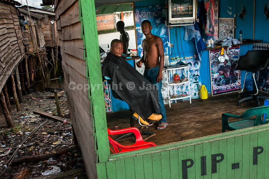 A Colombian hairdresser cuts a man's hair in a barber shop in a shanty town in Tumaco, Colombia, 18 June 2010.