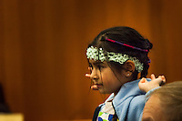 A young audience member mimics the arm and hand motions of dancers during an event celebrating the Lunar New Year.