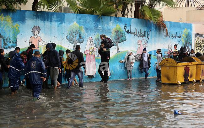 Palestinian school children walk in a flooded street during heavy rain in Gaza City on November 21, 2017. Photo by Ashraf Amra